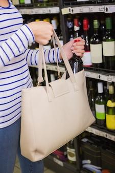 Femme mettant une bouteille de vin rouge sur son sac