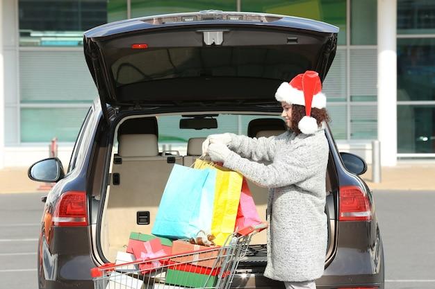 Femme mettant des cadeaux dans le coffre de la voiture à l'extérieur