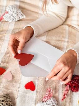 Femme mettant des coeurs dans une enveloppe