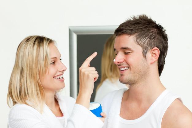 Femme mettant la crème sur le nez de son mari