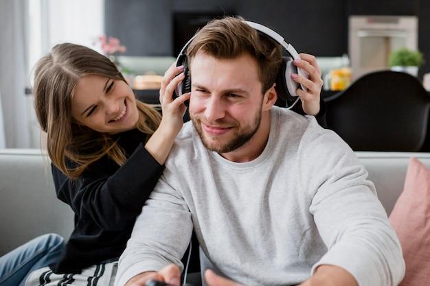 Femme mettant des écouteurs sur l'homme