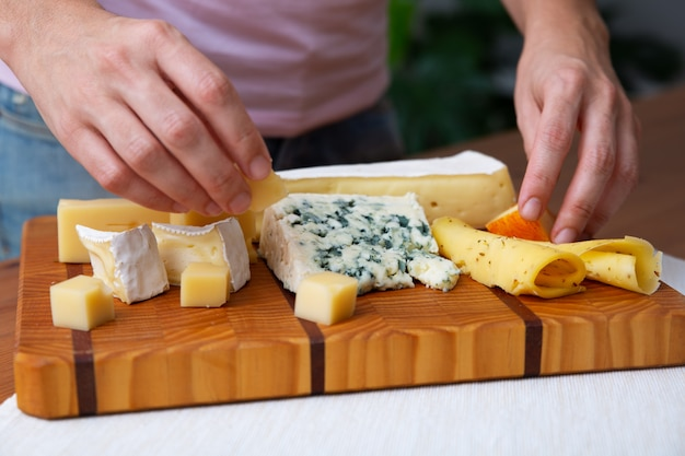 Femme mettant des fromages bleus, mous ou durs