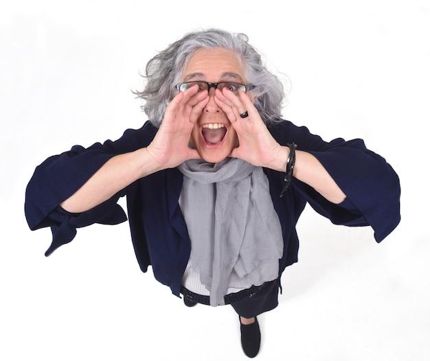Femme mettant une main dans la bouche et crie sur fond blanc
