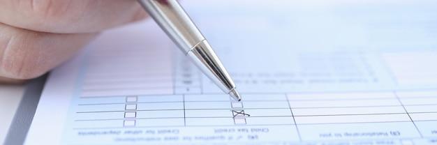 Femme mettant la marque avec le stylo à bille sur le plan rapproché de questionnaire