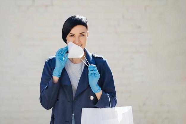 Femme mettant un masque de protection médicale dans la rue pendant l'épidémie de covid 19. protection en prévention de l'éclosion du virus de la grippe, épidémie. un concept du danger du coronavirus.