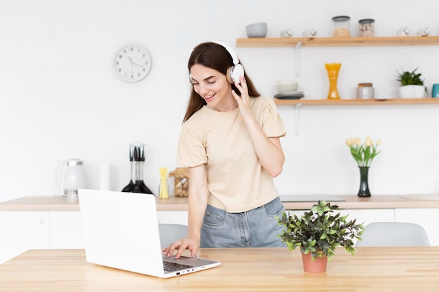 Femme mettant de la musique sur son casque à partir d'un ordinateur portable