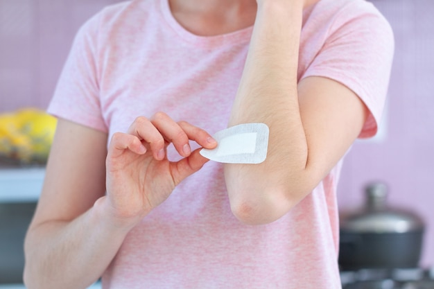 Femme mettant un pansement adhésif sur le coude blessé. premiers secours