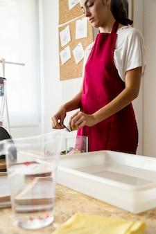 Femme mettant des papiers déchirés dans un récipient en verre
