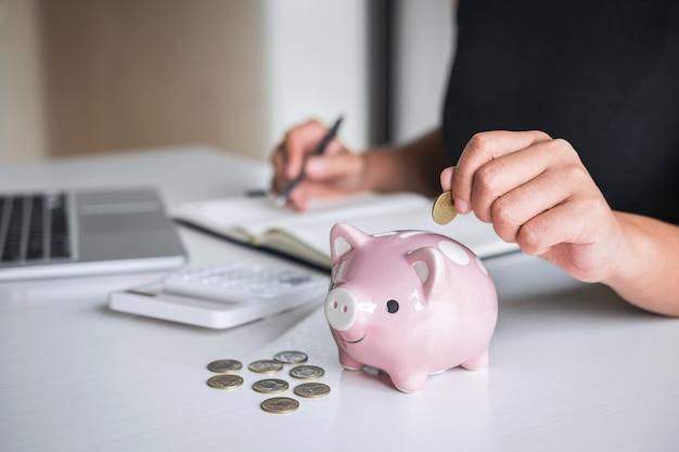 Femme mettant une pièce d'or dans une tirelire rose pour renforcer les affaires en croissance au profit et économiser avec la tirelire, économiser de l'argent pour le futur plan et concept de fonds de retraite