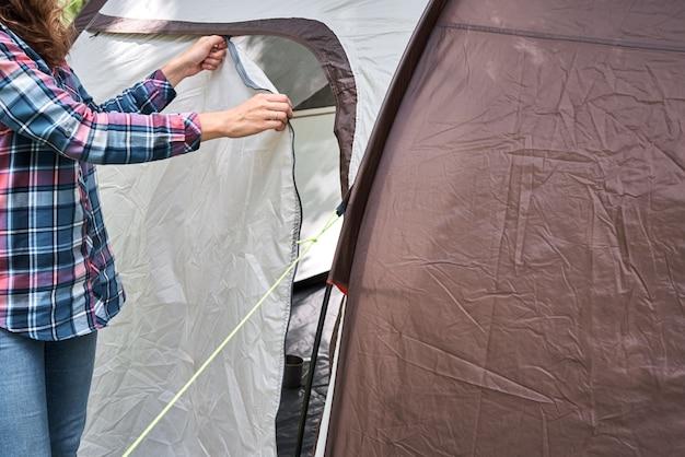 Femme mettant en place une tente de camping en forêt