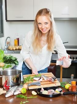Femme mettant des poissons tranchés dans une poêle à frire