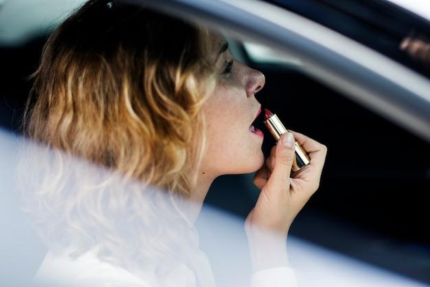 Femme mettant sur le rouge à lèvres dans une voiture