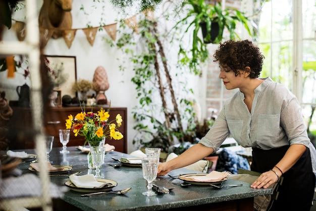 Femme mettant une table pour les clients