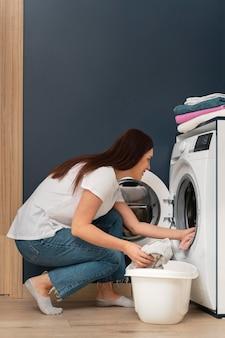 Femme mettant des vêtements sales dans la machine à laver