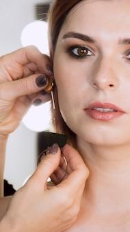 Femme, mettre, boucles d'oreilles, client