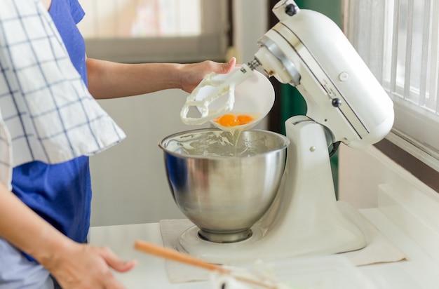 Femme, mettre, oeufs, électrique, stand, mélangeur, bol, cuisine, top