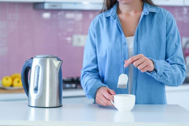 Femme, mettre, sachet thé, dans, a, tasse, et, utilisation, a, bouilloire électrique, pour, brassage, thé chaud, chez soi, à, cuisine