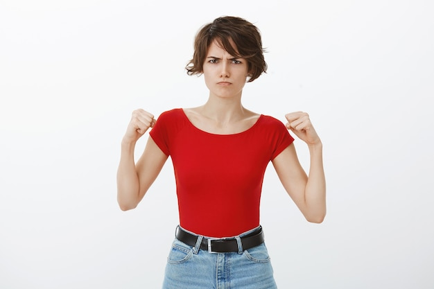 Femme mignonne en colère bouillante de colère, levant les poings et boudant folle