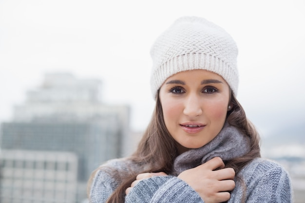Femme mignonne froide avec des vêtements d'hiver sur posant