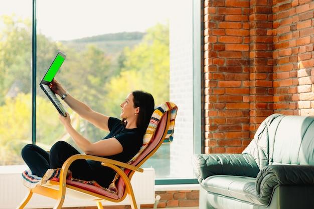 Femme mignonne et heureuse souriante et appel vidéo sur ordinateur portable assis dans un fauteuil à bascule confortable dans une atmosphère chaleureuse.