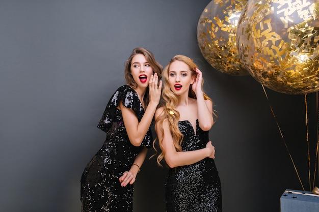 Femme mignonne intéressée aux cheveux blonds regardant ailleurs avec la bouche ouverte. portrait intérieur de jolie fille disant quelque chose à une amie à la fête.