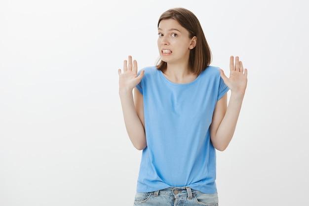 Femme mignonne maladroite levant les mains et serrant les dents embarrassées, se faire prendre