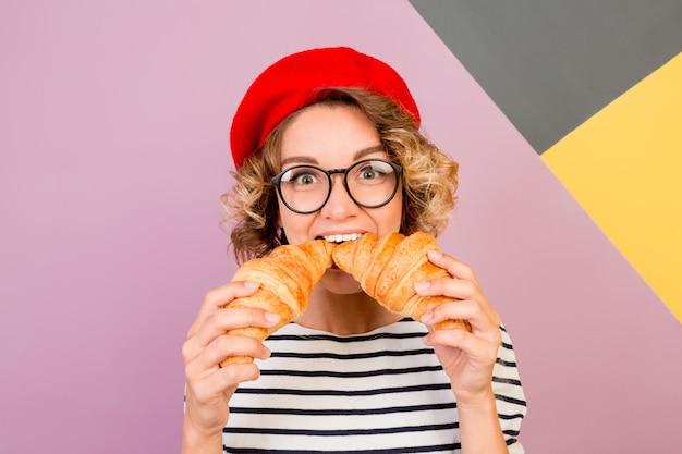 Femme mignonne rêveuse en béret rouge tenant de gros croissants savoureux dans les mains.
