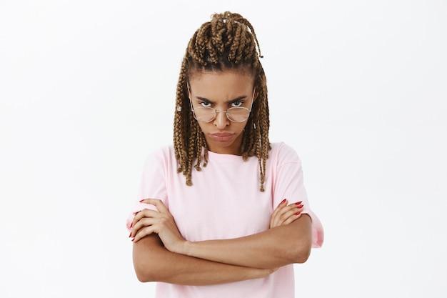 Femme mignonne ringard mécontente et stricte à la peau sombre et redoute à la recherche de sous le front avec un regard de condamnation