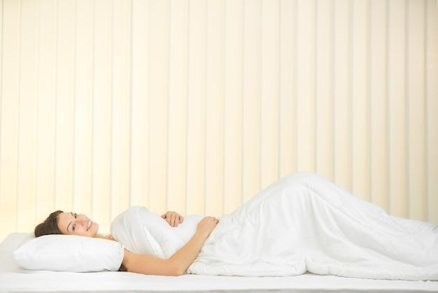 La femme mignonne s'allonge sur le lit et sourit