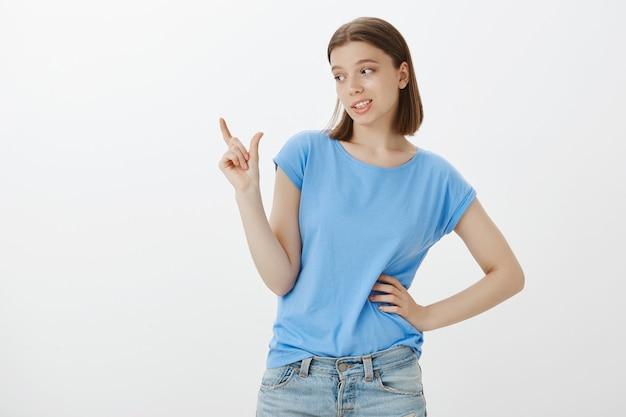 Femme mignonne sceptique faisant la moue et montrant quelque chose de trop petit, petite chose
