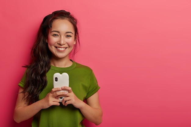 Femme mignonne souriante aux joues rouges heureuse de lire le message de l'amant, ne peut pas imaginer la vie sans les technologies modernes