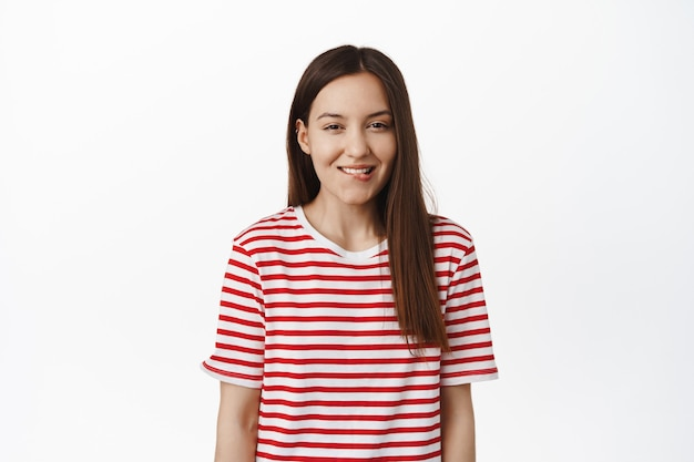 Femme mignonne souriante mordant la lèvre et plissant les yeux de la tentation, veut essayer une chose délicieuse, tentée par quelque chose, debout dans un t-shirt rayé contre un mur blanc.