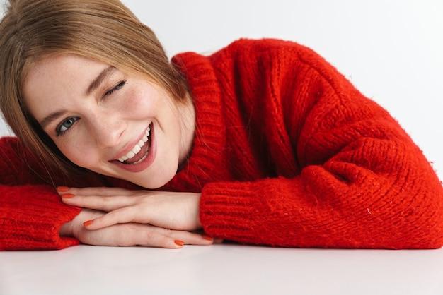 Femme mignonne souriante en pull rouge clignotant en s'appuyant sur une table isolée sur un mur blanc