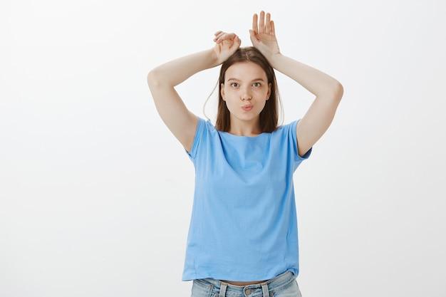 Femme mignonne et tendre faisant le geste des oreilles de lapin et à la stupide