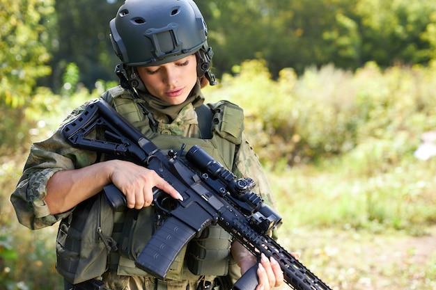 Femme militaire vérifie les détails de l'arme avant l'entraînement militaire, chargement du pistolet à l'extérieur, tir sportif