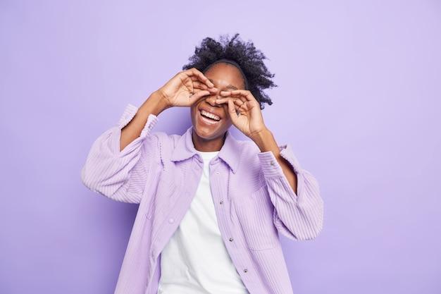 Une femme millénaire aux cheveux bouclés et insouciante garde les mains sur les yeux sourit positivement vêtue d'une chemise de velours