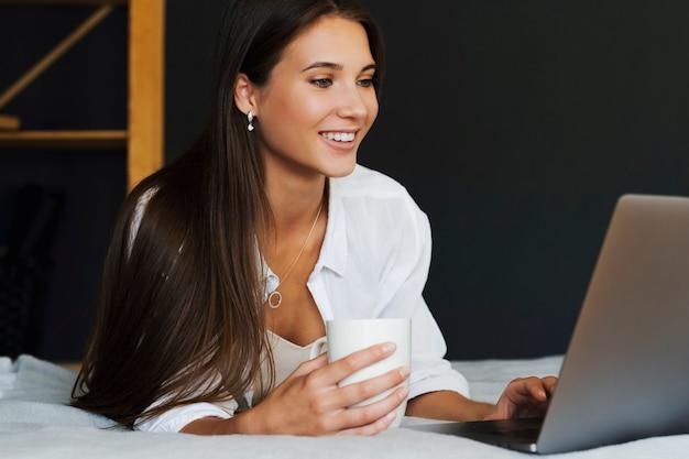 Femme millénaire est assise sur le lit en chemise blanche, tenant une tasse de café à la main, regardant l'écran du portable. belle femme brune utilise un ordinateur portable pour regarder du contenu en ligne, une formation en ligne, travailler à distance