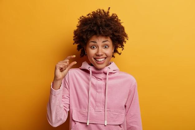 Une femme millénaire ethnique positive mesure un objet minuscule, sourit joyeusement