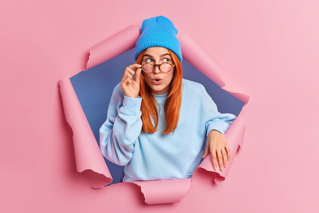 Une femme millénaire impressionnée regarde étonnamment au-dessus, garde la main sur des lunettes porte un pull bleu et un chapeau entend des nouvelles choquantes.