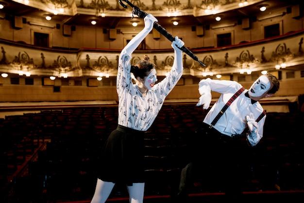 Femme mime artiste frappant le mime masculin avec un parapluie dans l'auditorium