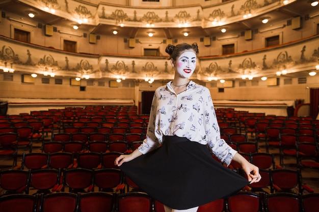 Femme mime debout dans un auditorium posant