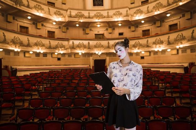 Femme mime debout dans la lecture de l'auditorium script