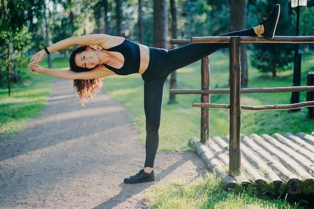 Femme mince active dans des vêtements de sport fait des exercices de pilates et s'étend en plein air