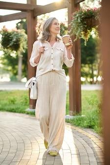 Femme mince adulte avec du café regardant des fleurs