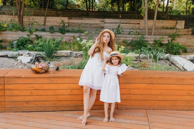 Femme mince aux pieds nus et sa fille en robe blanche debout sur un plancher en bois sur la nature. belle dame bien faite posant dans le parc avec petite nièce après le pique-nique.