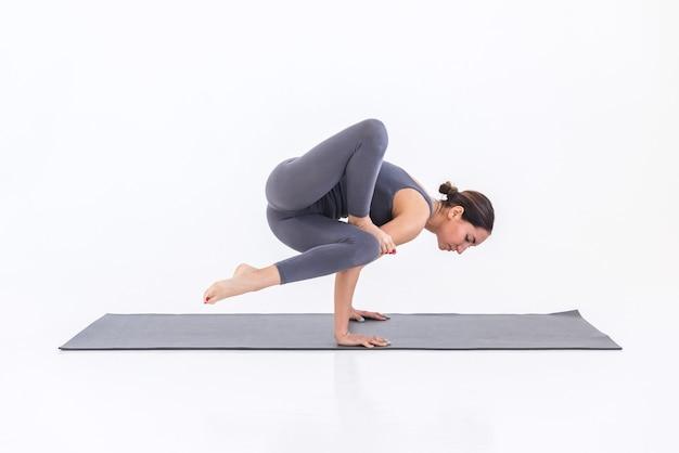 Femme mince caucasienne faisant du yoga sur le tapis sur fond blanc, debout sur ses mains