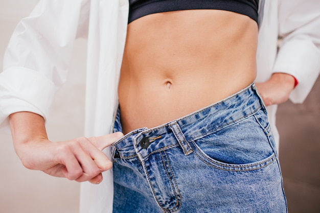 Une femme mince en chemise blanche et sous-vêtements noirs en jean taille plus grande montre une perte de poids réussie.
