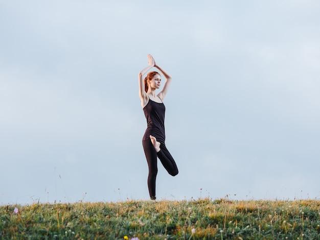 Une femme mince est engagée dans le yoga dans la nature dans les montagnes en leggings et un t-shirt