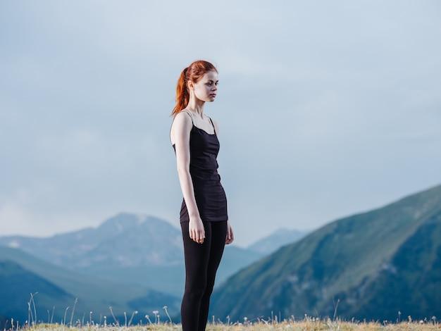 Une femme mince est engagée dans le yoga dans la nature dans les montagnes en leggings et un t-shirt.