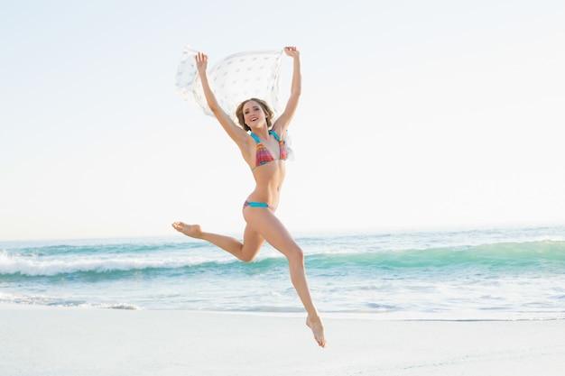 Femme mince euphorique sautant dans l'air en tenant le châle